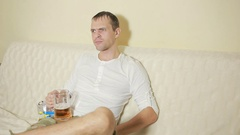 Young man drinking beer at home couch and watching television Stock Footage