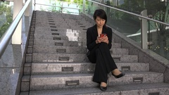 Relax For Asian Businesswoman Texting With Smartphone Sitting On Stairs Stock Footage