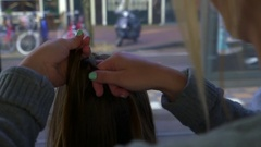 Closeup Of Young Woman Braiding Her Friend's Hair On Moving Train Stock Footage