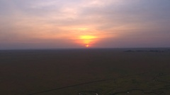 AERIAL: Endless Serengeti plains - a flat wilderness at dramatic golden sunset Stock Footage