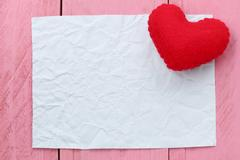 Red heart placed on paper note of empty for input text or message in design. Stock Photos