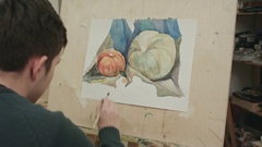 Young male student painting watercolor still life Stock Footage