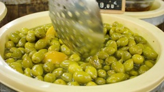Seller puts green olives with lemon Stock Footage