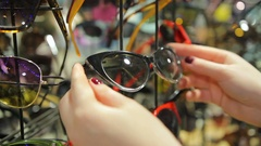 Accessories sale at local department store, female customer choosing sunglasses Stock Footage