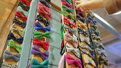 Woman choosing handmade bow-tie among huge variety at handcraft store, fashion Stock Footage