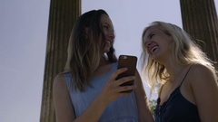 Friends Look Through Their Funny Vacation Photos On Their Smart Phone Stock Footage