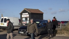 Cars & people at busy beach car park (slow pan) Stock Footage