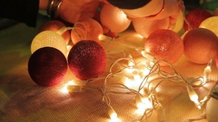Female hands assembling garland from handmade glowing balls, festive atmosphere Stock Footage