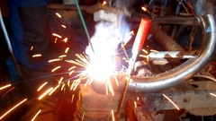 Assembly and repair of motorcycles in his garage. Welding iron parts. Stock Footage