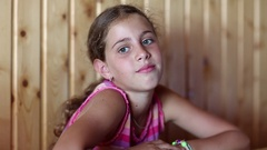 Pretty girl sits at the table and looks at the camera Stock Footage