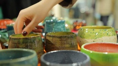 Lady choosing decorative handmade pottery bowls at ceramic store, shopping Stock Footage