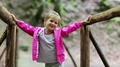 Little girl stands on a wooden bridge and smiles HD Footage