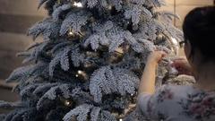 Brunette decorate Christmas tree with toy. View from back Stock Footage