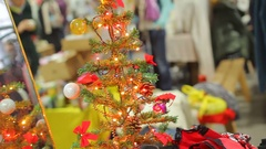 Small Christmas tree with bright garlands creating holiday atmosphere in store Stock Footage