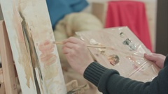 Male artist hands applying brush strokes on canvas and holding palette Stock Footage