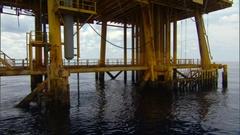 Tilt up to yellow oil platform Stock Footage