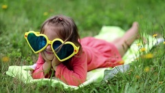 Funny little girl in sunglasses in shape of hearts lies on grass and grimaces Stock Footage