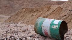 Iron barrel lies on the stony ground in Aqaba, Jordan Stock Footage