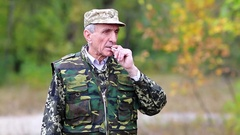 Senior man in military uniform smokes a cigarette in the forest Stock Footage