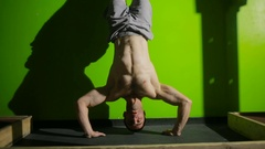 Athlete with naked torso doing push-ups on his hands while standing upside down Stock Footage