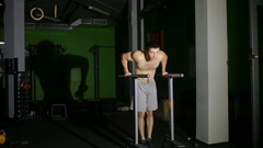 Muscular man bench performs on the uneven bars at the gym. Stock Footage