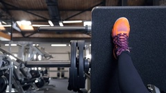Woman leg on trainers raising weight doing exercises in gym Stock Footage