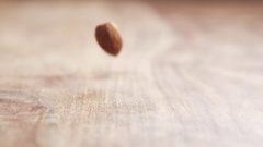 Almonds falling in slow motion on wooden table Stock Footage