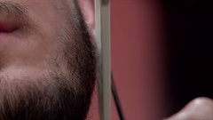 Young bearded man beard trimmed with scissors at salon Stock Footage