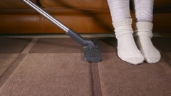 Vacuum cleaner nudging legs out of the way. Stock Footage