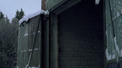 A large brick shed with an open gate on the roof snow Stock Footage