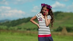 Pretty girl stands on the meadow and speaks on cell phone Stock Footage