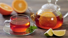 Glass teapot and cup of black tea with orange, lemon, lime and mint on a wooden Stock Footage