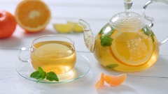 Glass teapot and Cup with green tea, orange, Mandarin, lime and mint on white Stock Footage