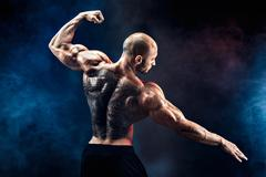 Unrecognizable muscular man with tattoo on back against of black background Stock Photos