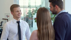 Salesman shakes hands with customer at the car dealership Arkistovideo