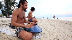 Musician playing an instrument called Handpan or Hang drum at sunset , Thailand Stock Footage