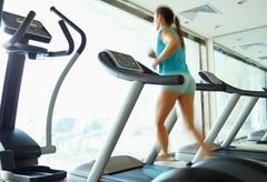 Woman running on treadmill in gym Stock Photos