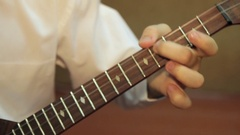 A boy learns to play the balalaika, close up Stock Footage