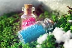 Two Glass bottles with purple stars and blue hearts in the forest. Stock Photos
