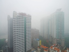 High residential buildings next to  road in smog Stock Footage