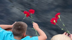 Red carnation flowers in the hands of a boy on a background of water Stock Footage