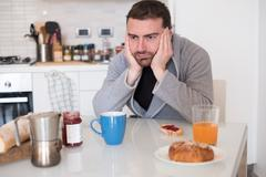 Tired man feeling bad during the morning breakfast Stock Photos
