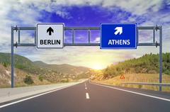 Two options Berlin and Athens on road signs on highway Stock Photos