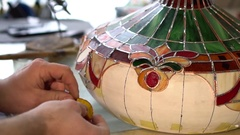 Master makes Tiffany stained glass lamp, try on a piece of glass to light form Stock Footage