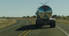 Following a Chrome Tanker Semi Truck Driving in the Desert By Wind Turbines Stock Footage