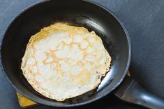 Stack of pancakes on frying pan. Stock Photos