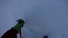 A man ice climbing with ice axes on a snow covered mountain. Stock Footage