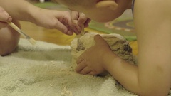 Family playing in the archeology destroys the plaster to get the skeleton Stock Footage