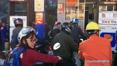 Motorbikers wait at gas station during the morning rush hour, Vietnam Stock Footage