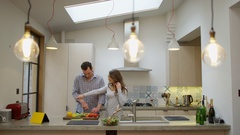 4K Happy affectionate couple dancing while preparing a meal in kitchen at home Stock Footage